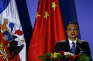Chinese Premier Li Keqiang delivers a speech with Chile's President Bachelet during an opening ceremony of an economic forum in Santiago city